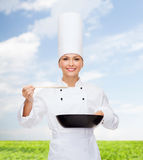 Smiling female chef with pan and spoon. Cooking and food concept - smiling female chef with pan and spoon tasting food stock images