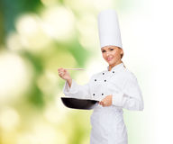 Smiling female chef with pan and spoon. Cooking and food concept - smiling female chef with pan and spoon tasting food stock image