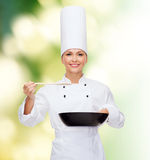 Smiling female chef with pan and spoon. Cooking and food concept - smiling female chef with pan and spoon tasting food stock photos