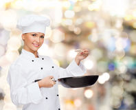Smiling female chef with pan and spoon Royalty Free Stock Photos