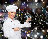 Smiling female chef with pan and spoon Stock Photos