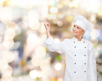Smiling female chef pointing finger to something Stock Image