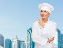 Smiling female chef pointing finger to sonething Stock Image
