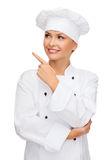 Smiling female chef pointing finger to sonething Royalty Free Stock Photography