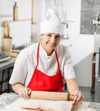 Smiling Female Chef Rolling Pasta Sheet At Counter Stock Image