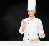 Smiling female chef with salad on plate Stock Images
