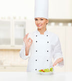 Smiling female chef with salad on plate Stock Photo
