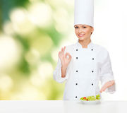Smiling female chef with salad on plate Royalty Free Stock Photo