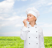 Smiling female chef showing delicious sign Stock Images
