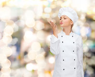 Smiling female chef showing delicious sign Stock Photos