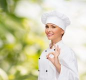 Smiling female chef showing ok hand sign Stock Photo