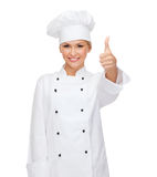 Smiling female chef showing thumbs up Stock Image