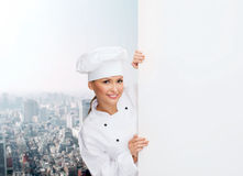 Smiling female chef with white blank board Royalty Free Stock Photos