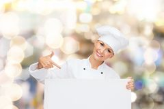 Smiling female chef with white blank board Stock Photo