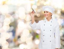 Smiling female chef writing something on air. Cooking, advertisement and people concept - smiling female chef, cook or baker with marker writing something on air royalty free stock image