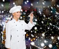 Smiling female chef writing something on air. Cooking, holidays, advertisement and people concept - smiling female chef, cook or baker with marker writing Stock Photo