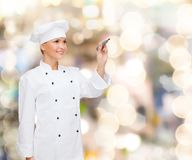 Smiling female chef writing something on air Stock Photo