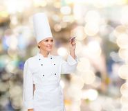 Smiling female chef writing something on air. Cooking, holidays, advertisement and people concept - smiling female chef, cook or baker with marker writing royalty free stock photos