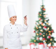 Smiling female chef writing something on air. Cooking, holidays, holidays, advertisement and people concept - smiling female chef with marker writing something Stock Photography