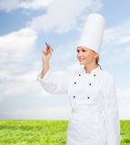 Smiling female chef writing something on air. Cooking, new technology , advertisement and food concept - smiling female chef with marker writing something on stock photo