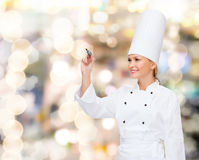 Smiling female chef writing something on air. Cooking, new technology , advertisement and food concept - smiling female chef with marker writing something on royalty free stock photography