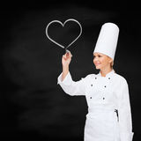 Smiling female chef writing something on air. Cooking, new technology , advertisement and food concept - smiling female chef with marker writing something on Stock Images
