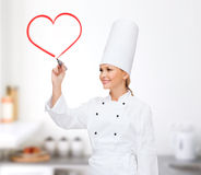 Smiling female chef writing something on air. Cooking, new technology , advertisement and food concept - smiling female chef with marker writing something on royalty free stock photo