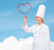 Smiling female chef writing something on air. Cooking, new technology , advertisement and food concept - smiling female chef with marker writing something on stock photos