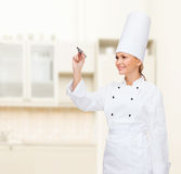 Smiling female chef writing something on air. Cooking, new technology , advertisement and food concept - smiling female chef with marker writing something on royalty free stock image