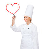 Smiling female chef writing something on air. Cooking, new technology , advertisement and food concept - smiling female chef with marker writing something on Royalty Free Stock Photos