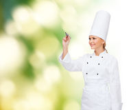 Smiling female chef writing something on air. Cooking, new technology , advertisement and food concept - smiling female chef with marker writing something on stock image