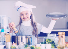 Smiling female child in chef cap making bouillon in kitchen Royalty Free Stock Photography