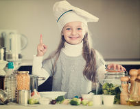 Smiling female child in chef cap with vegetables in kitchen Royalty Free Stock Image