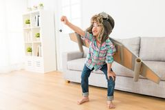 Smiling female children wearing astronaut costume. Smiling sweet female children wearing astronaut costume making ready to fly gesture standing on living room stock photography