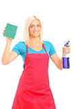 Smiling female cleaner holding a sponge and spray stock photo