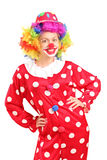Smiling female clown in a red costume posing. Isolated against white background Royalty Free Stock Photo