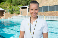 Smiling female coach standing near poolside. Portrait of smiling female coach standing near poolside at the leisure center Stock Photo