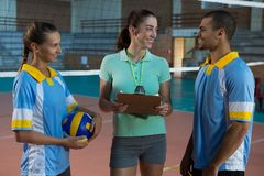Coach talking with volleyball players at court Royalty Free Stock Photography