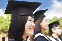 Smiling female college graduate standing with classmate. On campus stock photo