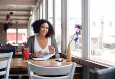 Smiling female college student sitting at cafe with pencil and book Royalty Free Stock Images