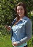 Smiling Female College/University Student Outdoors, Holding Cell Phone Mobile Phone. This image shows a smiling young woman who is a college or university Royalty Free Stock Image