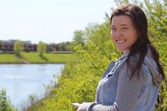 Smiling Female College/University Student Outdoors Near Campus Pond with Cell Phone Mobile Phone. This horizontal image shows a young woman who is a college or Royalty Free Stock Image