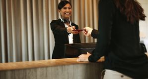 Concierge returning the documents to hotel guest. Smiling female concierge returning the documents to hotel guest after check-in process. Female client receiving stock photos