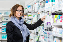 Smiling Female Consumer Choosing Product In. Portrait of smiling female consumer choosing product in pharmacy Stock Image