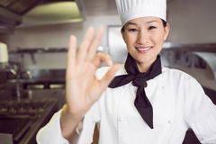 Smiling female cook gesturing okay sign in kitchen Stock Photo