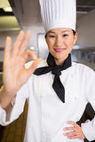 Smiling female cook gesturing okay sign in kitchen Royalty Free Stock Photos