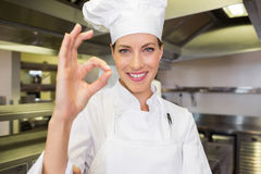 Smiling female cook gesturing okay sign in kitchen Royalty Free Stock Photography