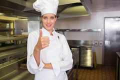 Smiling female cook gesturing thumbs up in kitchen Royalty Free Stock Image