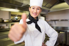 Smiling female cook gesturing thumbs up in kitchen Royalty Free Stock Photography