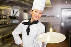 Smiling female cook holding empty plate in kitchen Royalty Free Stock Photo